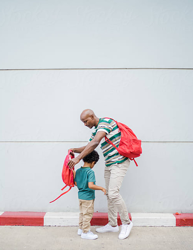 Father and Son putting backpacks on