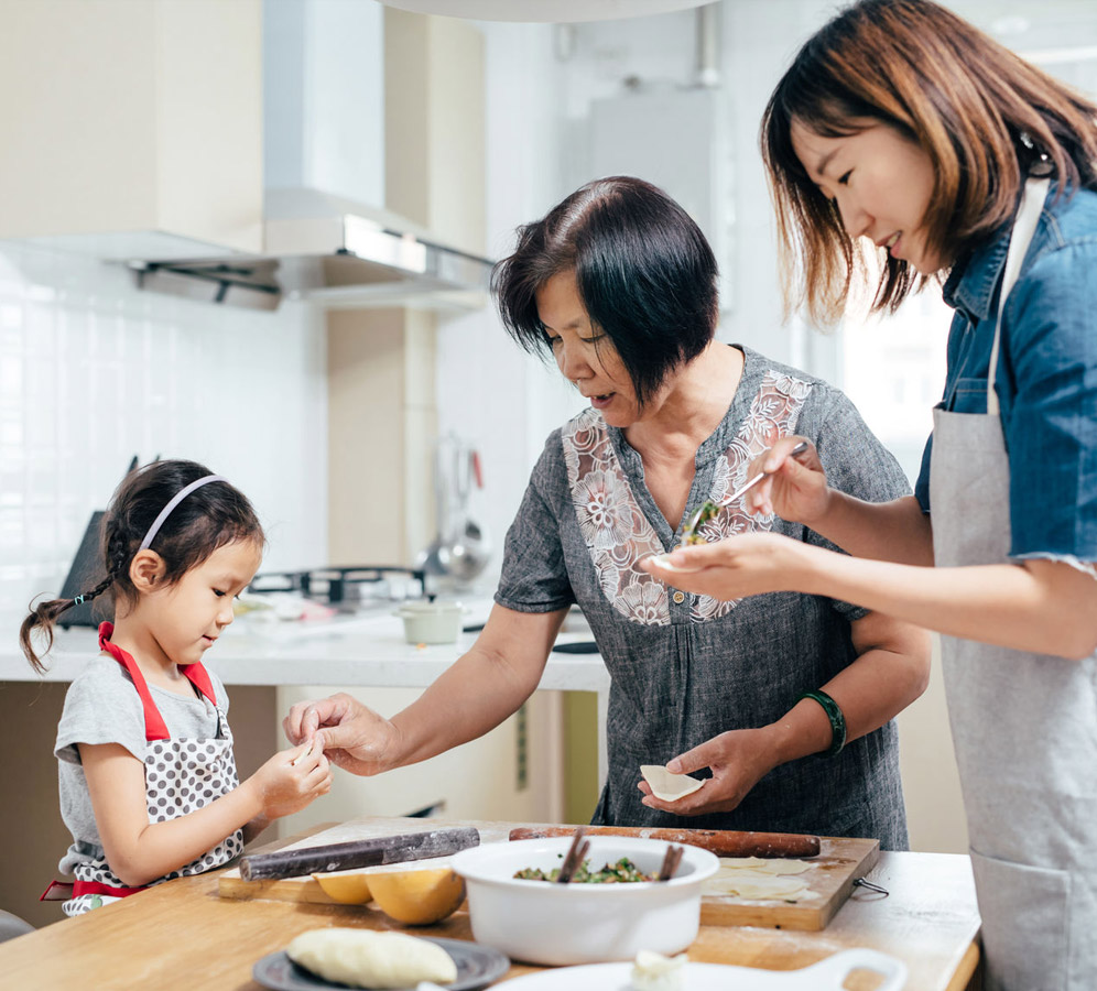 Little girl and her mother cooking with grandma